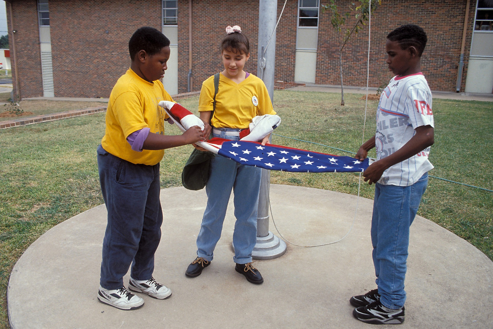 Two African-American boys and one Anglo girl lowering and folding Texas and United States flags at the end of the school day at Webb Junior High school.<br /> ©Bob Daemmrich/