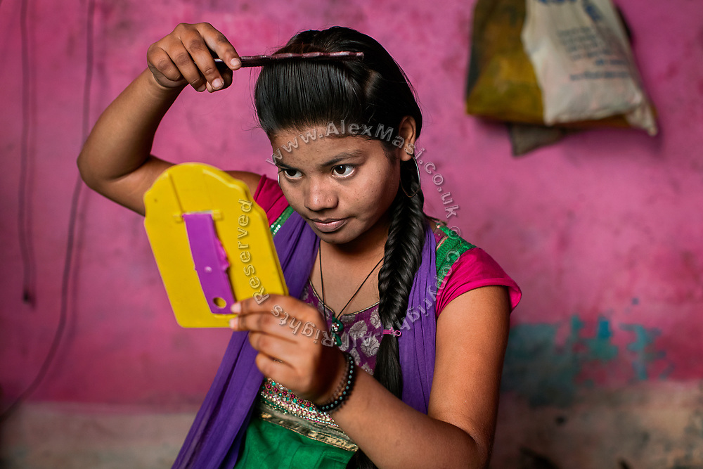 Poonam, 14, is combing her hair while sitting on the floor of her newly built home in Oriya Basti, one of the water-contaminated colonies in Bhopal, central India, near the abandoned Union Carbide (now DOW Chemical) industrial complex, site of the infamous '1984 Gas Disaster'.