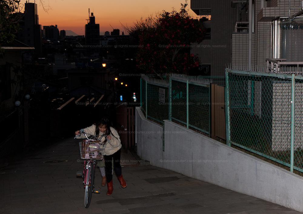 A Japanese girl push a bike during sunset over Fujimizaka (Mount Fuji viewing Hill) in Nishi Nippori, Tokyo, Japan. Friday January 11th 2013. This is the last street level place in central Tokyo to see Mount Fuji and is threaten with development that will block the view of this iconic peak.