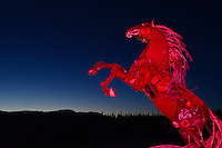 The Whitehorse Horse illuminated with red lighting against the pre-dawn sky