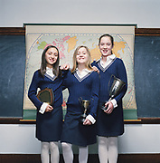 Three girls (9-11) standing in classroom, holding trophies, portrait