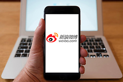 Using iPhone smartphone to display logo of Weibo, , Chinese microblogging site - hybrid of Facebook and Twitter