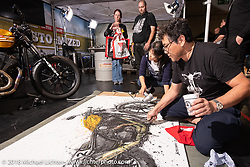 Makoto Endo painting (with chopsticks) the official Marcus Walz Intermot Customized  bike during the Intermot International Motorcycle Fair. Cologne, Germany. Wednesday October 3, 2018. Photography ©2018 Michael Lichter.