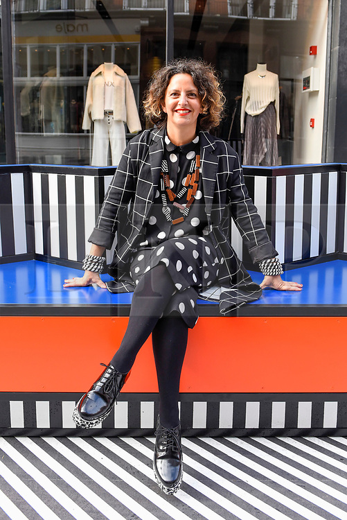 """© Licensed to London News Pictures. 12/09/2019. LONDON, UK.  Artist and designer Camille Walala, poses on one of her sculptural benches at the installation of """"Walala Lounge"""", where South Molton Street in Mayfair will be transformed into an urban living room.  10 sculptural benches, accompanied by planters and a series of oversized flags strung, bunting-style, from shopfront to shopfront, will convert the street into an immersive corridor of colour as part of this year's London Design Festival.  Photo credit: Stephen Chung/LNP"""