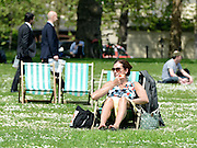 © Licensed to London News Pictures. 22/05/2012. London, UK A woman eats an apple whilst sitting on a deck chair in the sun in Hyde Park.  People enjoy the sunshine in London's Royal Parks today 22 May 2012. Photo credit : Stephen Simpson/LNP