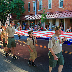 Lititz, PA / USA - July 3, 2017:   Boy scouts carry a large  US flag during a patriotic parade in a small American town at a 4th of July Independence Day celebration.