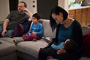 AUSTIN, TEXAS - FEBRUARY 9: Jinny Suh plays with her 4-month-old son while her husband and other son play a video game at their home in Austin, Texas on February 9, 2017. Jinny is a pro-vaccine advocate in addition to running her own businesses from home and raising her two sons. (Photo by Cooper Neill for The Washington Post)