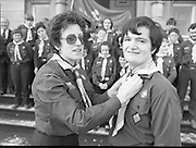 Scout Inducted Using Sign Language.   (P6)..1981..08.12.1981..12.08.1981..8th December 1981..Joe Needham, a deaf and dumb resident in Stewart's Hospital, Palmerstown, Co Dublin was enrolled into the 43rd Dublin (Palmerstown) unit of the Scouting Association of Ireland. The Chief Scout, Mr Joe McGough carried out the enrollment at the hospital. Ms Domenica Malocca, a teacher in the class for the deaf at the hospital, translated the Scout Promise into sign language during the ceremony...Image shows Joe Needham having his neckerchief adjusted by Scout Leader, Estelle Feldman at the steps of Stewart's Hospital.