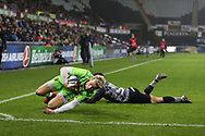 Harry Mallinder of Northampton Saints evades a tackle from Kieron Fonotia of the Ospreys to dive over and scores his teams 1st try in the 2nd half. European Rugby Champions Cup, pool 2 match, Ospreys v Northampton Saints at the Liberty Stadium in Swansea, South Wales on Sunday 17th December 2017.<br /> pic by  Andrew Orchard, Andrew Orchard sports photography.