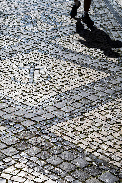 Walker with shadow and geometric tiles form shapes and patterns of wavy lines on paving stones in Aveiro, Portugal