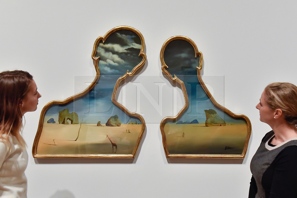 "© Licensed to London News Pictures. 03/10/2017. London, UK.   Staff members view ""Couple With Their Heads Full of Clouds"", 1937, by Salvador Dali at the preview of ""Dali / Duchamp"", a new exhibition of works by Salvador Dali and Michel Duchamp taking place at the Royal Academy of Arts in Piccadilly.  Over 80 artworks in different media are on display from 7 October to 3 January 2018.   Photo credit : Stephen Chung/LNP"