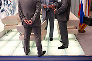 Faceless Russian delegates are in deep discussion in a hall at the Paris Air Show, Le Bourget France. With the flag of the Russian Federation strategically placed to the right of the stand, the three anonymous are secretively talking business in a group meeting, their crumpled suits show they have been working on this project for many hours or days. Two of the men have exchanged business cards to make new contacts. The Paris Air Show is a commercial air show, organised by the French aerospace industry whose purpose is to demonstrate military and civilian aircraft to potential customers.
