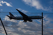 An American Airlines Boeing 777 landing at Heathrow airports north runway behind the boundary security fence.  Heathrow Airport, London.