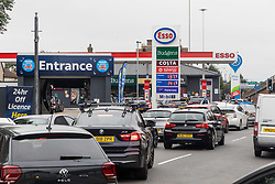 Licensed to London News Pictures. 25/09/2021. London, UK. Large queues form on the second day of the fuel crisis at an Esso petrol station on the A3 near New Malden, south-west London today as desperate motorists stop to fill up. Yesterday, petrol stations across London and the South East were on critical levels with many running out of fuel as oil giants struggle to maintain deliveries due to the lack of HGV drivers. Photo credit: Alex Lentati/LNP