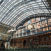 The southern end of the distinctive iron and glass arched cover over the platforms of St Pancras Railway Station (now known as St Pancras International). The renovated station features distinctive Victorian architecture and serves as a Eurostar terminal for high-speed trains to Europe. There are also platforms for domestic train services. The distinctive train shed roof was designed by William Henry Barlow.