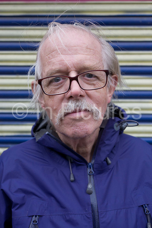 A close-up portrait of an elderly man in his seventies street portrait with moustache. The man has stubble on his chin and his mostache is also untidy, in need of a trim and his white hair spills across his balding forehead and on to his glasses frames. A close-up portrait of an elderly man in his seventies street portrait with moustache. The man has stubble on his chin and his moustache is also untidy, in need of a trim and his white hair spills across his balding forehead and on to his glasses frames.