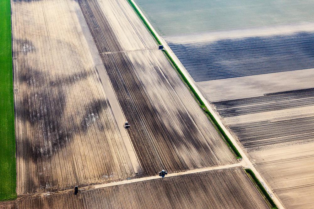 Nederland, Flevoland, Biddinghuizen, 01-05-2013; tractoren aan het werk op gedeeltelijk beregende akkers. Biddingringweg, zuidwestelijk van Biddinghuizen.<br /> Tractors pulling furrows in the vast fields.<br /> luchtfoto (toeslag op standard tarieven);<br /> aerial photo (additional fee required);<br /> copyright foto/photo Siebe Swart