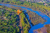 A hot air balloon floating low above the Rio Grande River during the Albuquerque International Balloon Fiesta, Albuquerque, New Mexico USA.