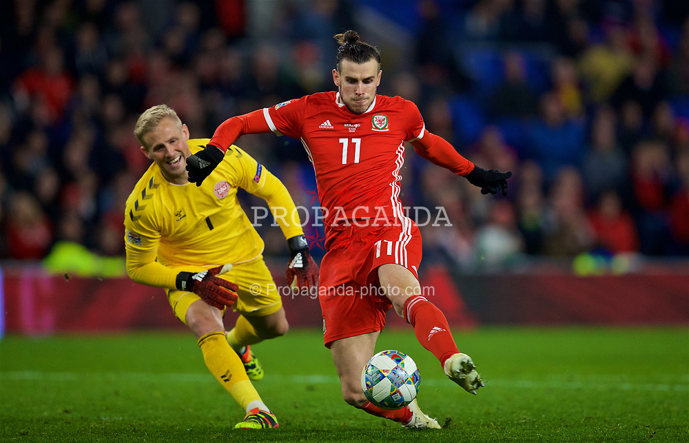 CARDIFF, WALES - Friday, November 16, 2018: Wales' Gareth Bale beats Denmark's goalkeeper Kasper Schmeichel as he scores a consolation goal during the UEFA Nations League Group Stage League B Group 4 match between Wales and Denmark at the Cardiff City Stadium. Wales lost 2-1.(Pic by David Rawcliffe/Propaganda)