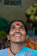 A woman looks to the sky at the beginning of monsoon rains, Goa, India.