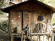 """A Laoseng minority woman sits outside her home in remote and roadless Ban Watai, Phongsaly Province, Lao PDR.  The villagers of Ban Watai wait to hear when and where they will be relocated and joined with three other Laoseng villages following the construction of the Nam Ou Cascade Hydropower Project Dam 5. The Nam Ou river connects small riverside villages and provides the rural population with food for fishing. It is a place where children play and families bathe, where men fish and women wash their clothes. But this river and others like it, that are the lifeline of rural communities and local economies are being blocked, diverted and decimated by dams. The Lao government hopes to transform the country into """"the battery of Southeast Asia"""" by exporting the power to Thailand and Vietnam."""