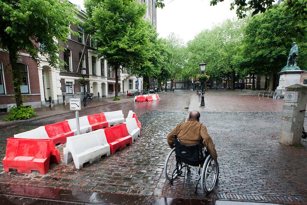 Een man in een rolstoel rijdt over het Domplein voorbij een wegversmalling