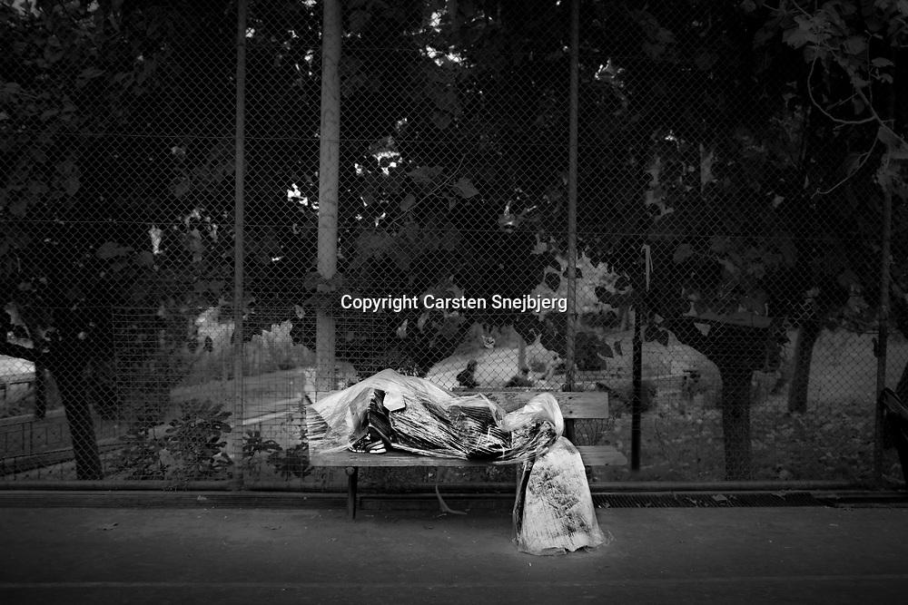 Migrant sleeping in park.