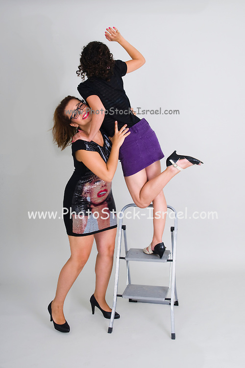 A young woman supports another on a step ladder almost falling