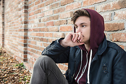 Young man sitting against brick wall and thinking, Munich, Bavaria, Germany