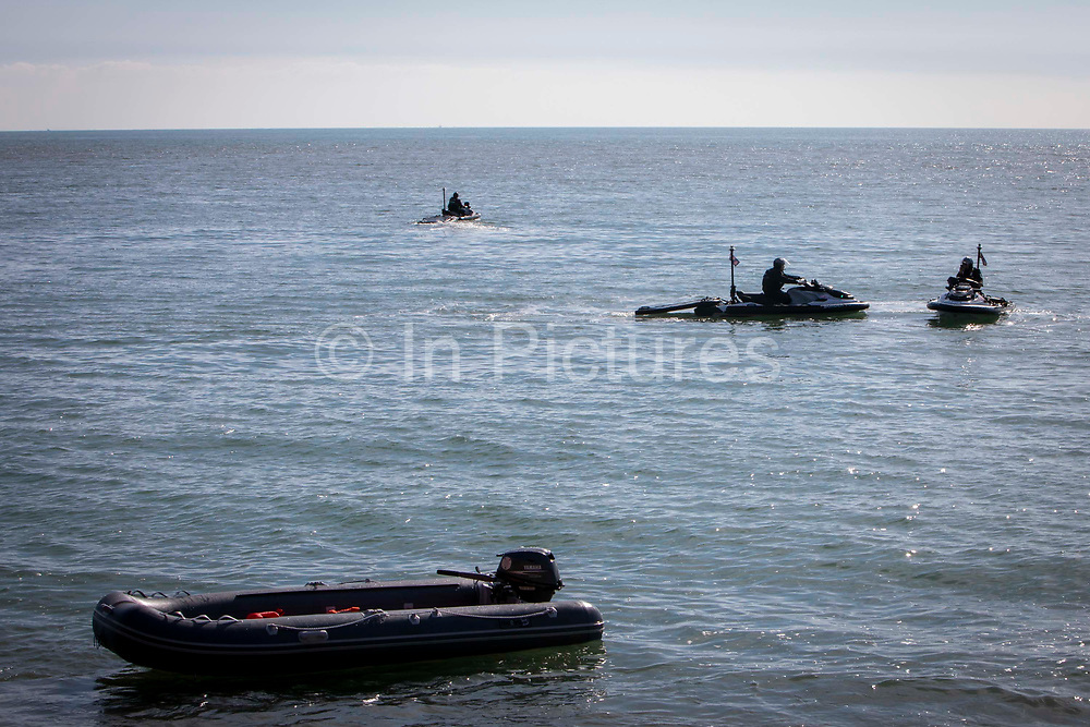Border Force officers use personal water crafts to monitor the removal of a dinghy from the sea that brought 13 Asylum seekers safely to the beach on the 8th of October 2021 in Folkestone, United Kingdom. The Home Office has begun using Jet Ski's or personal water crafts to move along the coast quicker and intercept small boats used by asylum seekers to cross the channel from France.