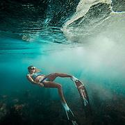 Female Freediver swimming under waves in clear blue water near Kailua Kona, Big Island, Hawaii.