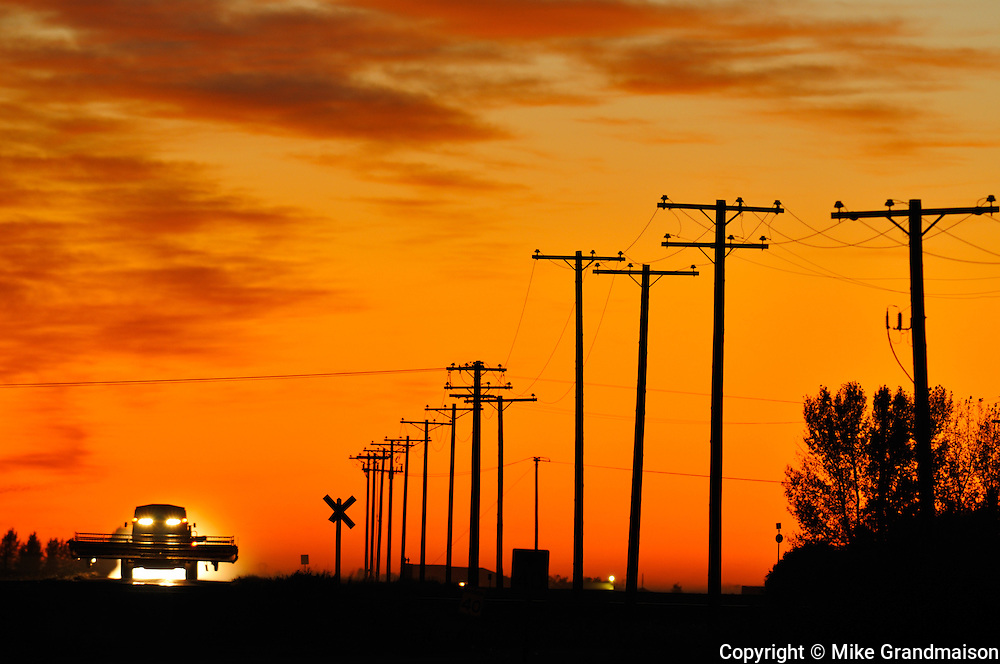 Combine moving down the road at sunset<br /> Tuxford<br /> Saskatchewan<br /> Canada
