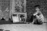 A boy sits next to his missing father's picture in Velika Krusa/Krusha e Mahde, Kosovo. Over 50 of the village's men were killed and burned by Serb forces; their bodies have not been identified.