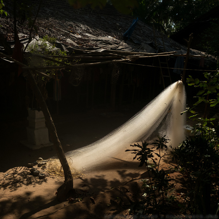 The white fishing net of a fisherman hangs in front of  house.