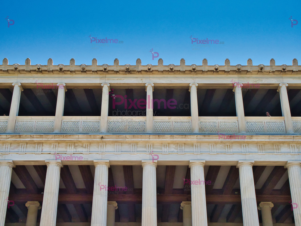 From below exterior of white Stoa of Attalos landmark in Athens with blue sky in background