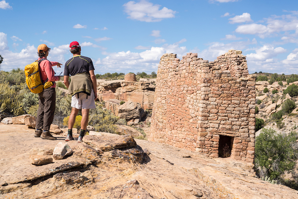 Hikers looking at Twin Towers, ancestral puebloan structures in Hovenweep National Monument, Utah.