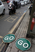 Two GO traffic road signs lie by the road near a queue of traffic in East Dulwich, on 26th April 2018, in London, England.