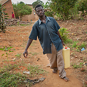 CAPTION: Damyano is seen here carrying water from a borehole pump to his home. Despite being extremely hearing impaired, blind in one eye and mute, he has married and now has two children, and indicates through sign language that he leads a happy life, largely thanks to the help of SignHealth Uganda. LOCATION: Kankamba Village, Lwengo District, Central Region, Uganda. INDIVIDUAL(S) PHOTOGRAPHED: Damyano Kato.