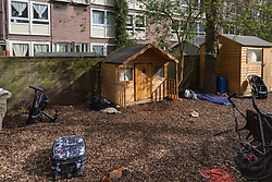 A small wooden wendy house in a section of an allotment reserved as a children's play area appears to have become the residence or storage shed of a homeless individual, whilst outside damaged luggage and rain soaked clothes and abandoned strollers are strewn around the area. Munster Square, Camden, March 18 2019.