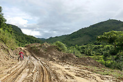 A man on a motorbike struggles to drive along the muddy main road from Sam Tai to Muang Kuan during rainy season, Houaphan province, Lao PDR