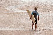 A surfer surveys the water at Waimea Bay.