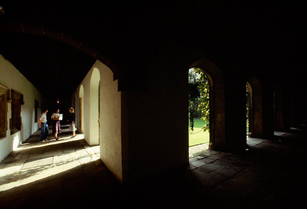 Students stroll along cloisters at Jesus College, Cambridge University, England, UK