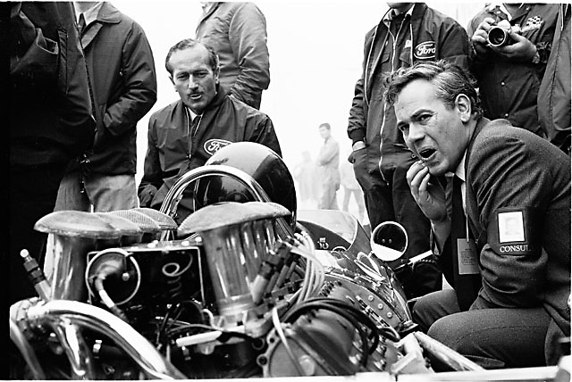 Keith Duckworth (right, hand to chin), designer of the Ford Cosworth DFV engine and Lotus head Colin Chapman (smiling at driver) conferring with driver Jim Clark at 1967 USGP at Watkins Glen.