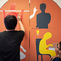 """Xavier Bellson, 14, right, watches classmate Jonathan Bellson, 14, left work on their mural representing the """"Holistic Wellbeing"""" section of the Six Directions Indigenous School's Mission Statement, Friday, Jan. 11, in Gallup. Their mural shows a wellness wheel which is something the school teaches to help students identify goals from physical fitness and academic, to wellness and being engaged in their community."""