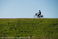 Rider on a bicycle path above Brat Style's flat track racing at West Point Offroad Village. Kawagoe, Saitama. Japan. Wednesday December 6, 2017. Photography ©2017 Michael Lichter.