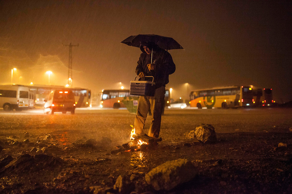 A Palestinian man is standing near a small bon fire to keep warm, while he waits for his pickup in Eyal crossing point near the Israeli city of Kfar-Saba.<br /> Each day Palestinian workers pass through cross points like this one in order to work in Israel.