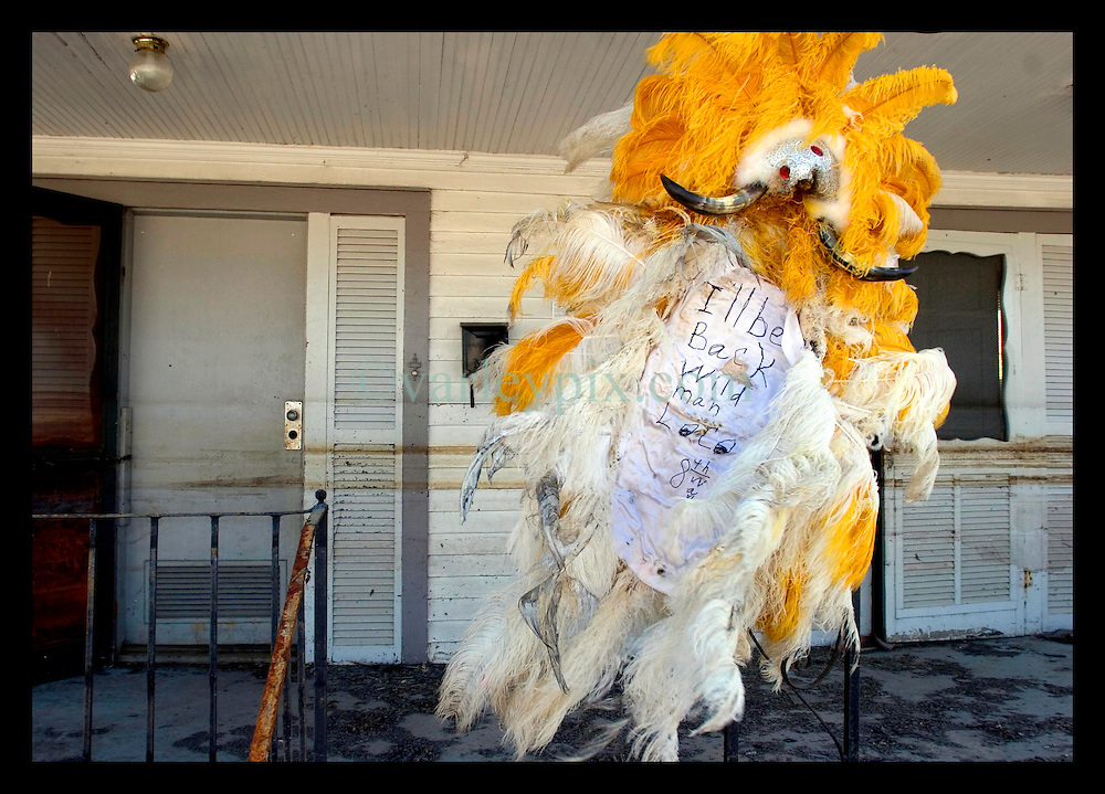 october 25th, 2005. Post Hurricane Katrina. New Orleans, Louisiana. The 8th ward lies in ruins following Katrina's devastating floods. The fabulous, somewhat dishevelled Mardi Gras Indian headress of Wild Man Loco is pinned defiantly to the outside of his home, clearly stating that 'I'll be back.'