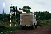 "Series I 86 inch Hard Top Land Rover with '""Safari Roof"",  by road distance sign, Northern Province, Zimbabwe Rhodesia, Southern Africa, 1960s"