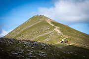 People making their way up Catstye Cam summit, west of Helvellyn mountain, The Lake District, Cumbria, United Kingdom on the 2nd of August 2021. Catstye Cam is connected to Helvellyn by Swirral Edge, one of the famous walking routes in the Lake District.