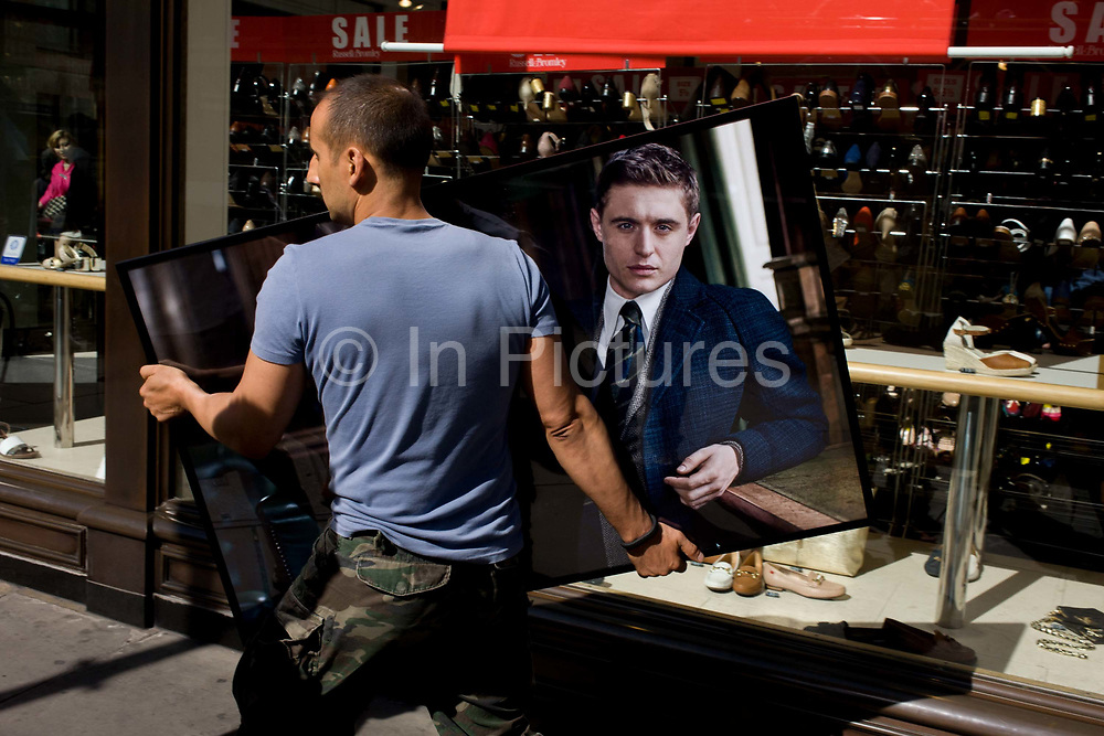 Worker carries a portrait of a male model, a fixture on its way to another premises in Soho, central London. The panel shows a well-dressed model leaning against a bar, the epitome of health, wealth, good looks and success. He seems to be staring at us while being transported along the street towards a nearby business where the picture is needed to decorate a retail wall. In the background is a show shop, displaying quality footwear while the model apparently looks on helplessly - as if being kidnapped.